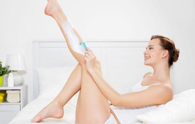 Женщина бреет ногу